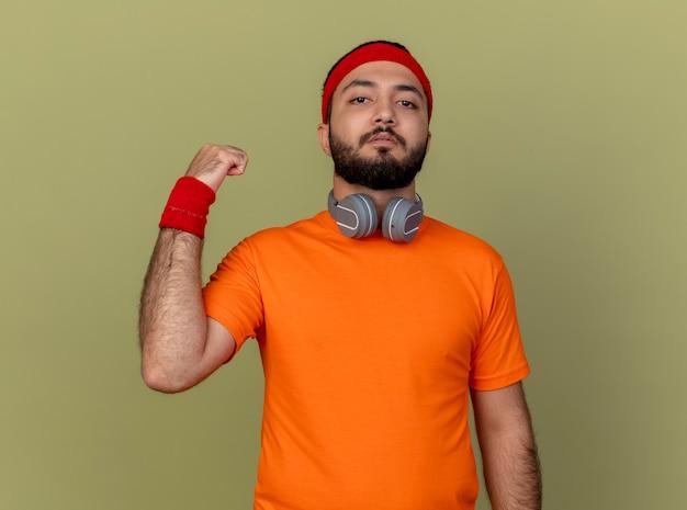 Zelfverzekerde sportieve jongeman met hoofdband en polsbandje met koptelefoon op nek tonen sterk gebaar geïsoleerd op olijfgroene achtergrond