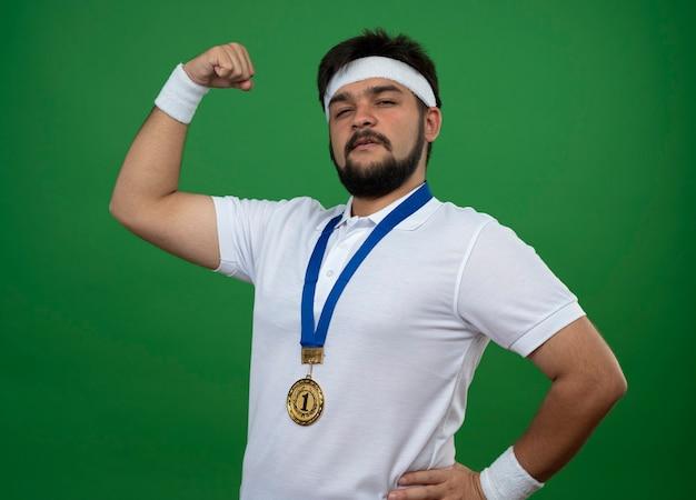 Zelfverzekerde sportieve jongeman met hoofdband en polsbandje met medaille met sterk gebaar geïsoleerd op groen