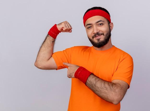 Zelfverzekerde sportieve jongeman met hoofdband en polsbandje met sterk gebaar geïsoleerd op een witte achtergrond