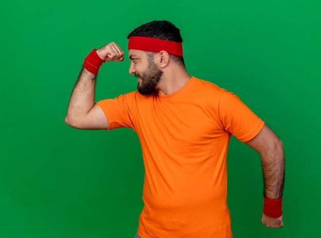 Zelfverzekerde sportieve jongeman met hoofdband en polsbandje met sterk gebaar geïsoleerd op groene achtergrond