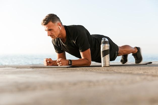 Zelfverzekerde sportman in oortelefoons die plank doet