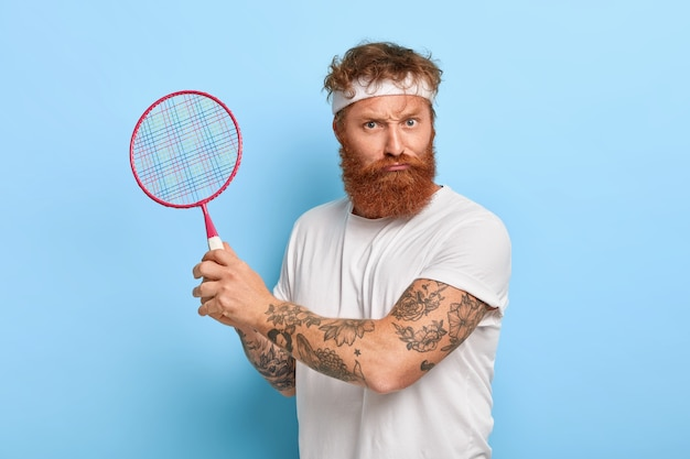 Zelfverzekerde sportman kijkt serieus, houdt tennisracket vast, heeft tatoeage op armen