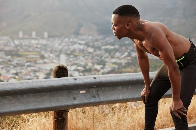 Zelfverzekerde sportman poseert halfnaakt, leunt met beide handen naar de schouders, voelt zich moe na cardiotraining, heeft een sterk lichaam, houdt van sport, modellen boven bergen met vrije ruimte.