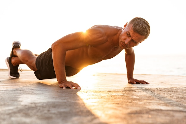 Zelfverzekerde sportman push-ups doen