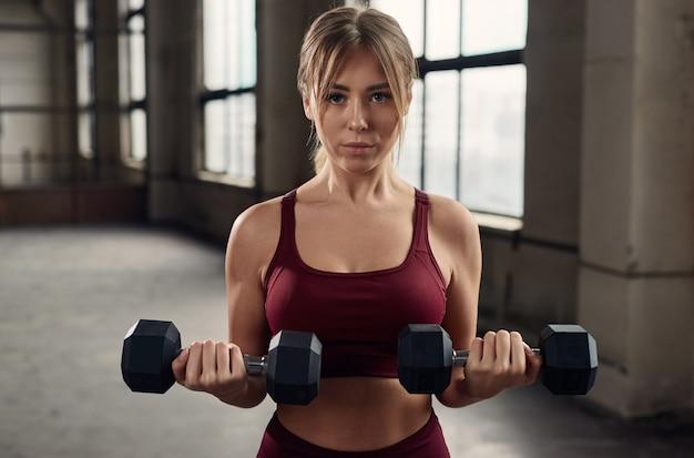 Zelfverzekerde sportvrouw trainen met halters