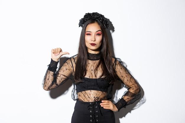 Zelfverzekerde stijlvolle aziatische vrouw die vastberaden kijkt, zwarte kanten jurk draagt voor halloween-feest, wijzend naar zichzelf brutaal, staande op een witte achtergrond.
