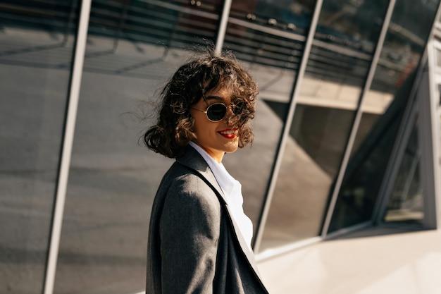 Zelfverzekerde stijlvolle vrouw met kort golvend haar gekleed in jas wandelen in de zakenwijk
