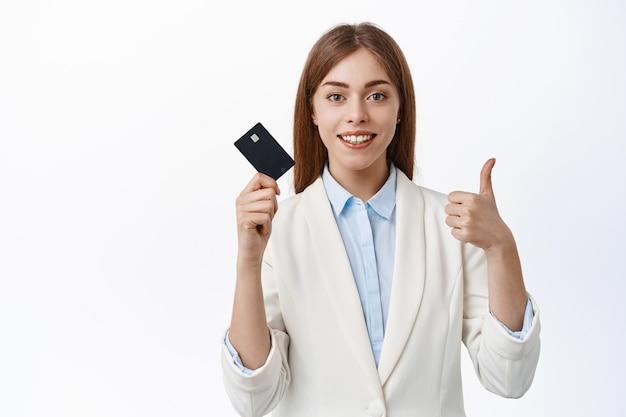 Zelfverzekerde, succesvolle zakenvrouw toont plastic creditcard en duimen omhoog, glimlacht tevreden, beveelt bank aan, staande over witte muur