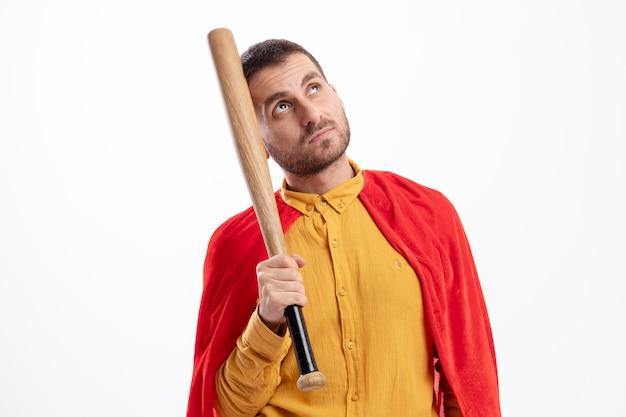 Zelfverzekerde superheld man met rode mantel houdt honkbalknuppel en kijkt omhoog geïsoleerd op een witte muur