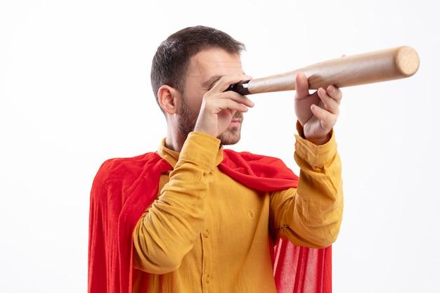Zelfverzekerde superheld man met rode mantel houdt honkbalknuppel voor zijn oog geïsoleerd op een witte muur