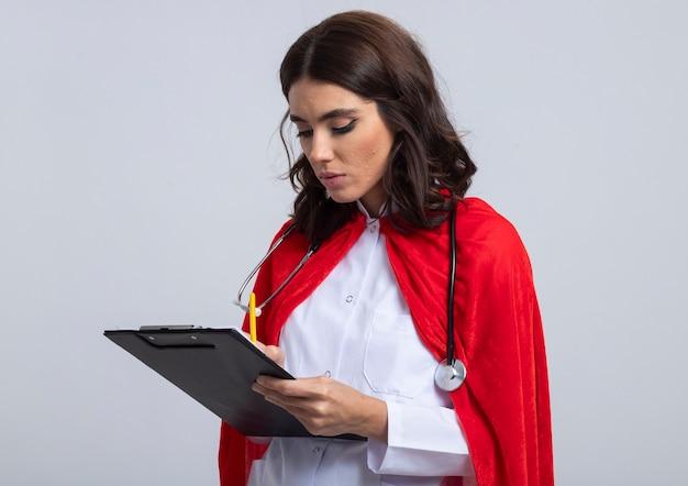 Zelfverzekerde supervrouw in artsenuniform met rode cape en stethoscoop schrijft op klembord met potlood dat op witte muur wordt geïsoleerd