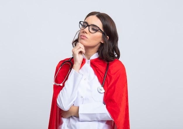 Zelfverzekerde supervrouw in doktersuniform met rode cape en stethoscoop in optische bril legt hand op kin en kijkt naar kant geïsoleerd op witte muur
