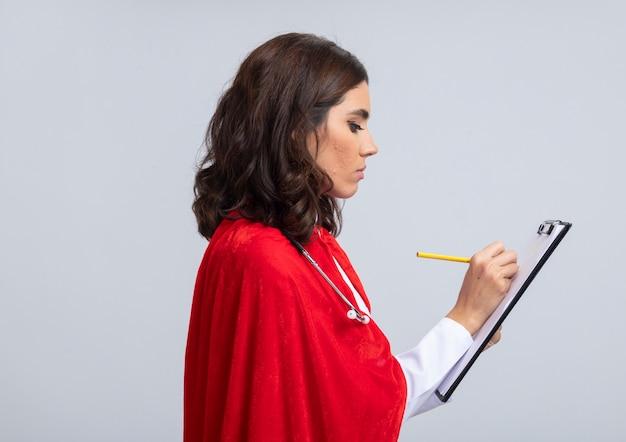 Zelfverzekerde supervrouw in doktersuniform met rode cape en stethoscoop staat zijwaarts met klembord en potlood geïsoleerd op een witte muur
