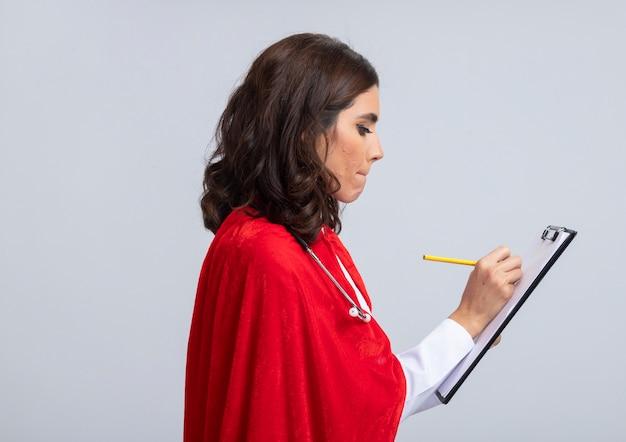 Zelfverzekerde supervrouw in doktersuniform met rode cape en stethoscoop staat zijwaarts schrijven op klembord met potlood geïsoleerd op een witte muur