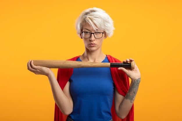 Zelfverzekerde supervrouw met rode cape die in optische glazen honkbalknuppel houdt en voorzijde bekijkt die op oranje muur wordt geïsoleerd