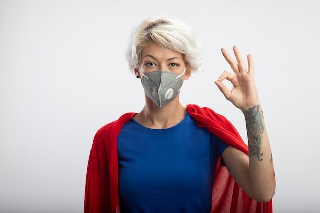 Zelfverzekerde supervrouw met rode cape die medische maskergebaren draagt ok handteken dat op witte muur wordt geïsoleerd