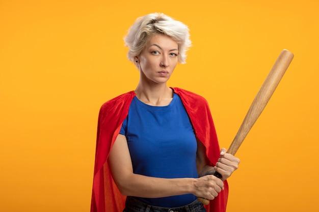 Zelfverzekerde supervrouw met rode cape houdt honkbalknuppel geïsoleerd op oranje muur
