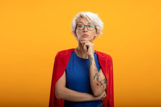 Zelfverzekerde supervrouw met rode cape in optische bril legt hand op kin geïsoleerd op oranje muur