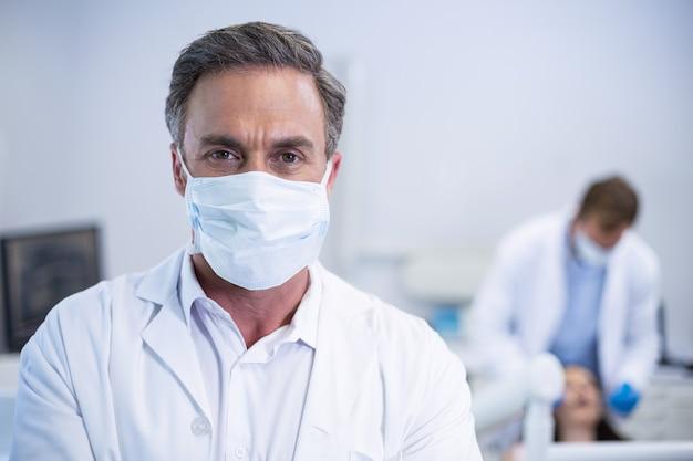 Zelfverzekerde tandarts in chirurgisch masker bij tandheelkundige kliniek