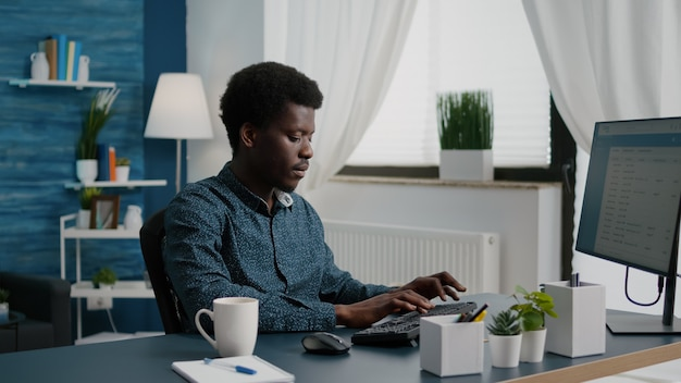 Zelfverzekerde telewerker die zijn werk vanuit huis doet en een slokje koffie neemt