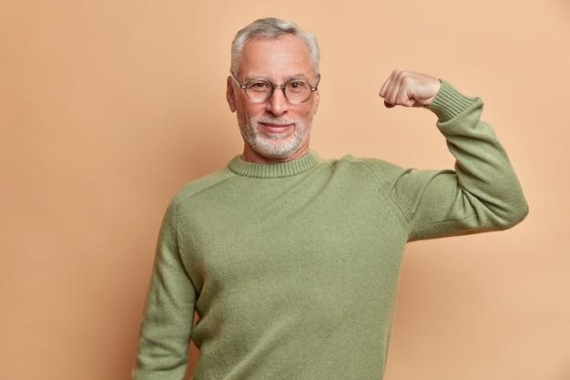 Zelfverzekerde tevreden grijsharige man heft arm op en toont spierresultaten nadat regelmatige training in de sportschool een bril en trui draagt die over bruine muur wordt geïsoleerd en trots op zichzelf is