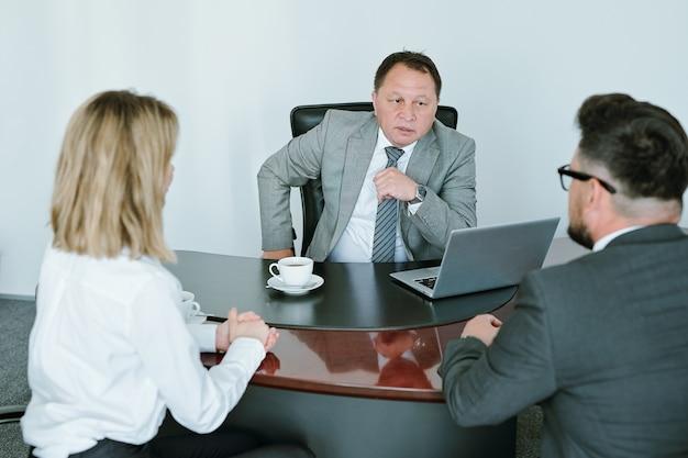 Zelfverzekerde volwassen baas in formalwear zittend in een stoel bij tafel voor twee ondergeschikten en hen raadplegen over hun taken