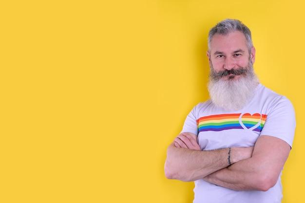 Zelfverzekerde volwassen bebaarde man gekleed met lgbtq symbolen t-shirt camera kijken, studio portret van homoseksuele man, gele achtergrond