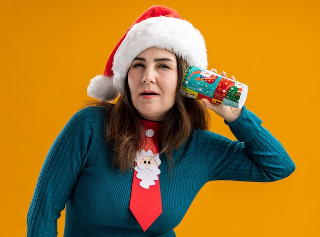 Zelfverzekerde volwassen blanke vrouw met kerstmuts en santa stropdas met papieren beker dicht bij oor geïsoleerd op een oranje achtergrond met kopie ruimte