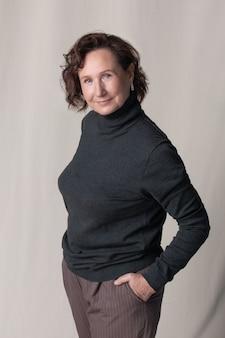 Zelfverzekerde volwassen blanke vrouw poseren in een stijlvolle polo-hals op een beige studio