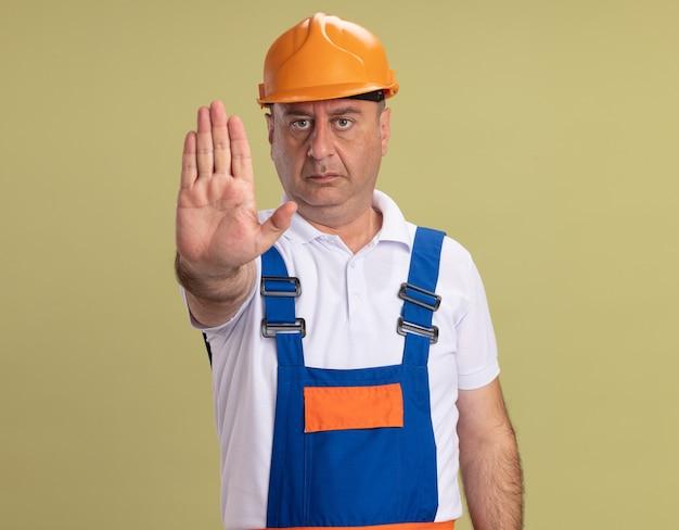 Zelfverzekerde volwassen bouwer man gebaren stoppen handteken geïsoleerd op olijfgroene muur