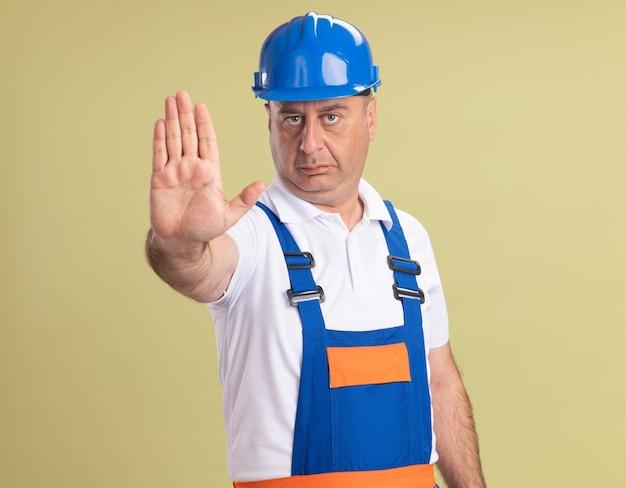 Zelfverzekerde volwassen bouwer man in uniforme gebaren stop handteken geïsoleerd op olijfgroene muur