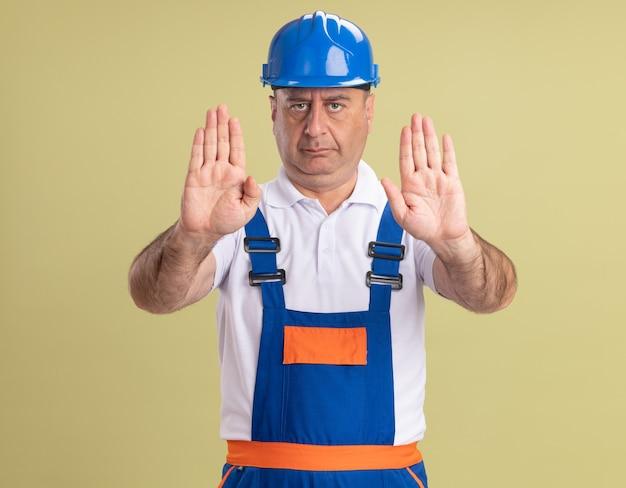 Zelfverzekerde volwassen bouwer man in uniforme gebaren stop handteken met twee handen geïsoleerd op olijfgroene muur