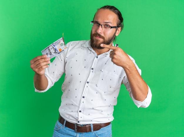 Zelfverzekerde volwassen knappe man met een bril die vasthoudt en wijst op een brandende dollar die naar een camera kijkt die op een groene muur is geïsoleerd