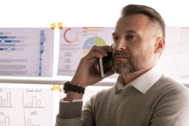 Zelfverzekerde volwassen makelaar die smartphone op het gehoor houdt terwijl hij met de klant praat met documenten op het whiteboard