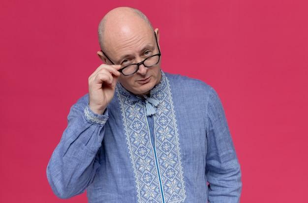 Zelfverzekerde volwassen man in blauw shirt die zijn bril vasthoudt en kijkt