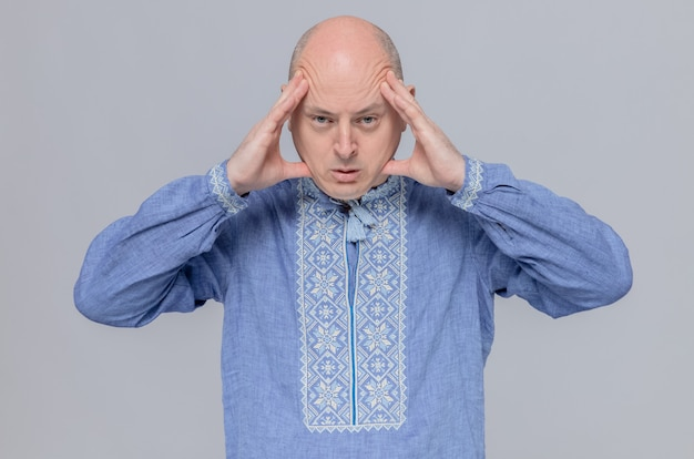 Zelfverzekerde volwassen man in blauw shirt die zijn hoofd vasthoudt en kijkt
