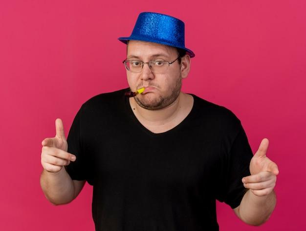 Zelfverzekerde volwassen man in optische bril met blauwe feestmuts wijst naar voren blazen feestfluitje geïsoleerd op roze muur