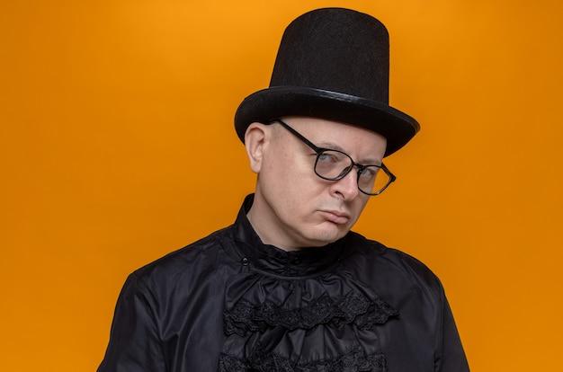 Zelfverzekerde volwassen man met hoge hoed en bril in zwart gotisch shirt