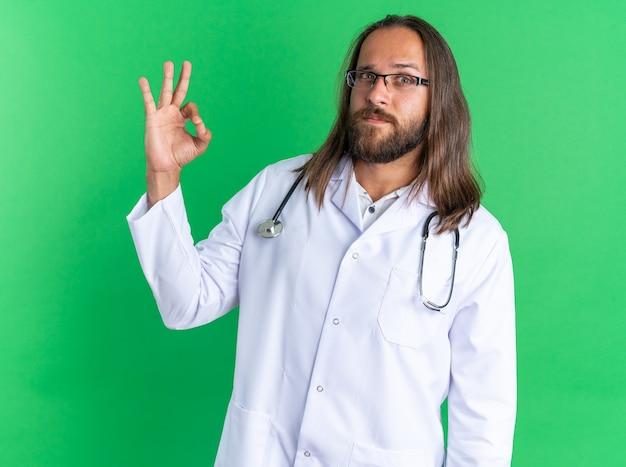 Zelfverzekerde volwassen mannelijke arts die een medisch gewaad en een stethoscoop draagt met een bril die naar de camera kijkt en een ok teken doet dat op een groene muur is geïsoleerd