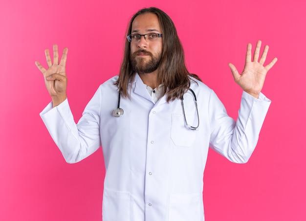 Zelfverzekerde volwassen mannelijke arts die medische mantel en stethoscoop draagt met een bril die naar een camera kijkt die negen toont met handen geïsoleerd op roze muur