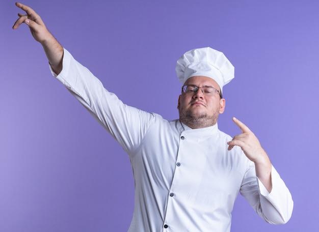 Zelfverzekerde volwassen mannelijke kok met een uniform van de chef-kok en een bril die naar de voorkant kijkt en omhoog wijst op een paarse muur
