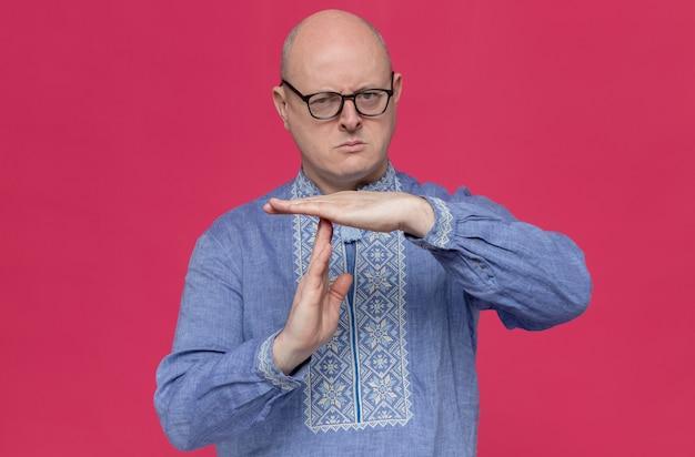Zelfverzekerde volwassen slavische man in blauw shirt met optische bril gebaren time-out teken