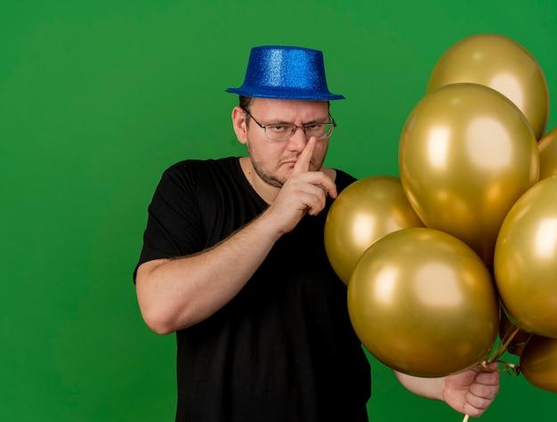 Zelfverzekerde volwassen slavische man in optische bril met blauwe feestmuts houdt heliumballonnen vast en gebaren stilteteken