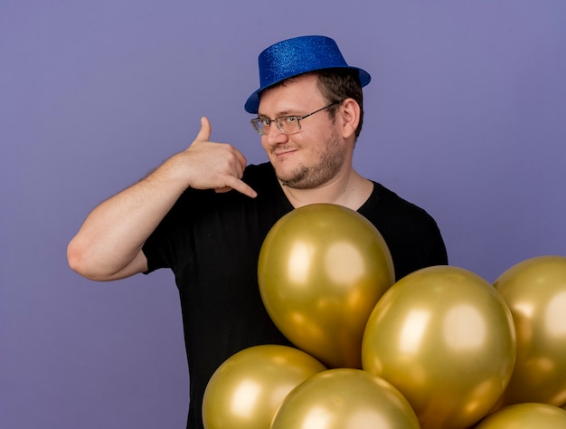 Zelfverzekerde volwassen slavische man in optische bril met blauwe feestmuts staat met heliumballonnen gebaren bel me teken