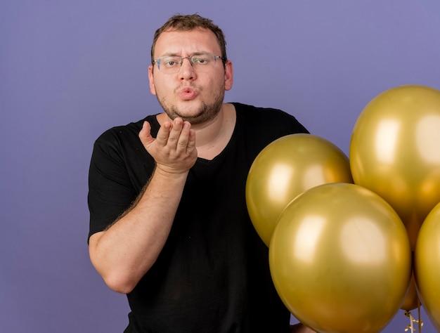 Zelfverzekerde volwassen slavische man in optische bril staat met heliumballonnen en stuurt kus met de hand