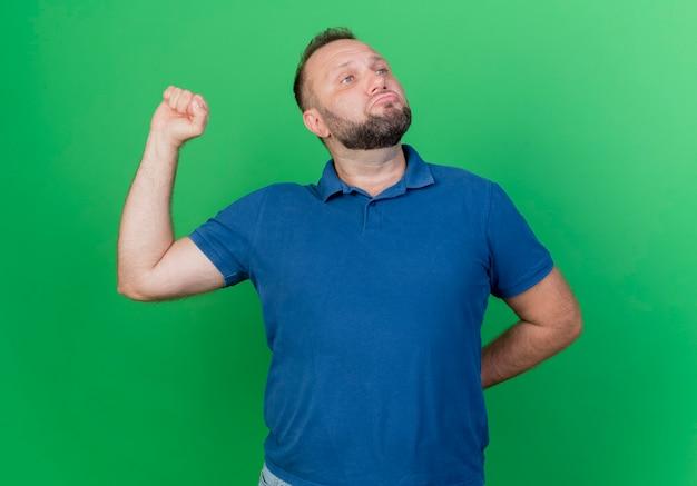 Zelfverzekerde volwassen slavische man kijken naar kant houden hand achter rug balde vuist geïsoleerd op groene muur