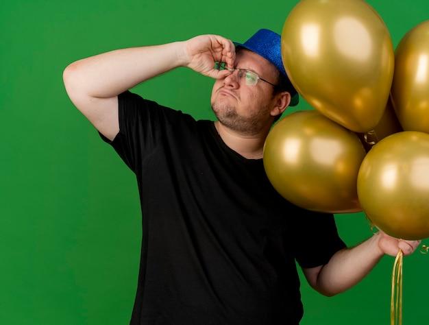 Zelfverzekerde volwassen slavische man met een optische bril met een blauwe feestmuts houdt heliumballonnen vast en kijkt door de vingers naar de zijkant