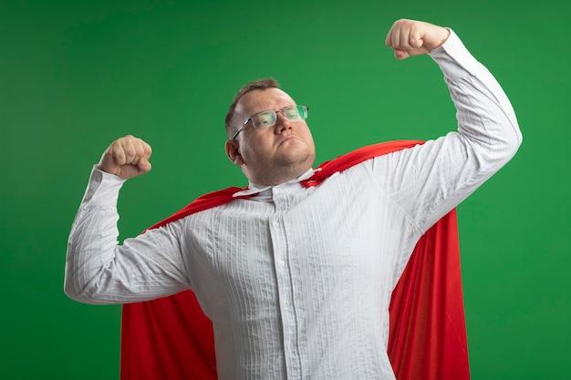 Zelfverzekerde volwassen slavische superheld man in rode cape bril doen sterk gebaar kijken kant geïsoleerd op groene muur