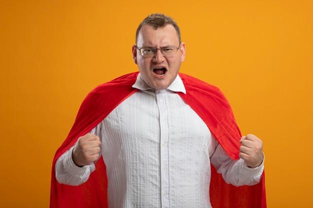 Zelfverzekerde volwassen slavische superheld man in rode cape bril gebalde vuisten geïsoleerd op oranje muur