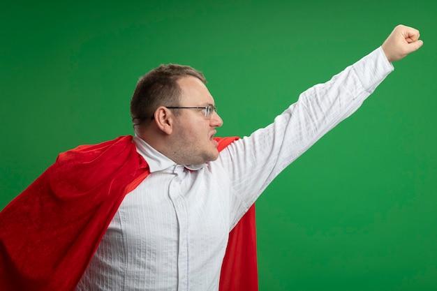 Zelfverzekerde volwassen slavische superheld man in rode cape bril kijken kant verhogen vuist omhoog geïsoleerd op groene muur